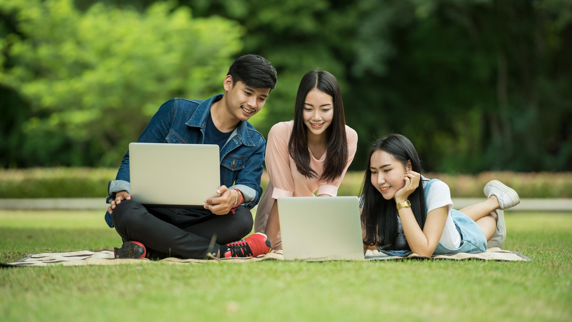 Three teenagers in park on laptops